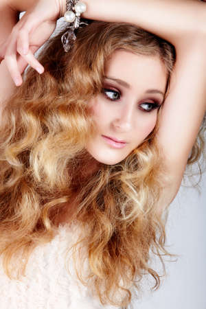 beautiful strawberry blond woman with green eyes and long big curly hair with arm over head looking down. photo