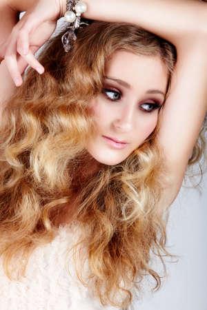loose hair: bella donna bionda fragola con gli occhi verdi e capelli ricci lungo grandi con braccio guardando oltre head.