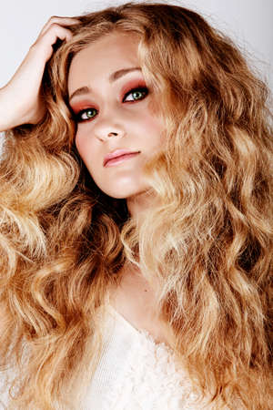 beautiful strawberry blond woman with green eyes and long big curly hair with hand in hair looking at camera.