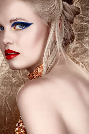 beautiful blond with hair in upstyle wearing dark fashion eyeshadow and red lips looking over shoulder on gold background in sepia fashion effect. photo