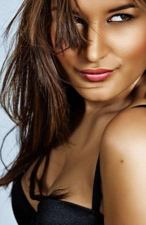glad vacker latin kvinna med färska naturliga make-up och långt brunt hår blåser i vinden