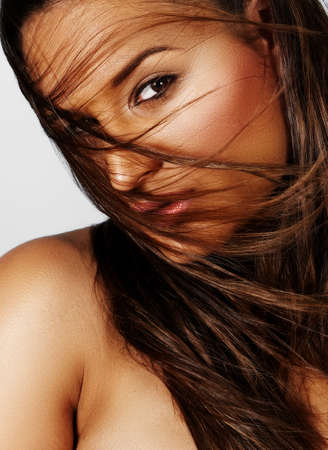 beautiful young woman of latin ethnicity with long brown hair blowing in wind. Stock Photo