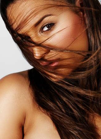 belle jeune femme d'origine ethnique latino avec de longs cheveux bruns soufflant dans le vent. Banque d'images
