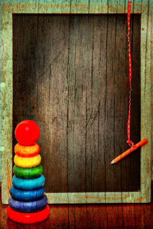 block note: empty grunge blackboard in a wooden texture antique frame with a pencil on a string next to a colorful  pyramid.
