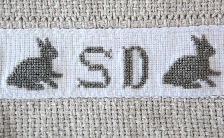 punto croce: Sigla inglese e bunny ricamato sul cotone grigio coperta utilizzando cross - stitch tecnica di ricamo.
