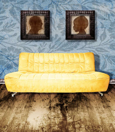 family living room: family portraits in grunge frames over a yellow couch against wallpaper background and wooden antique floor.
