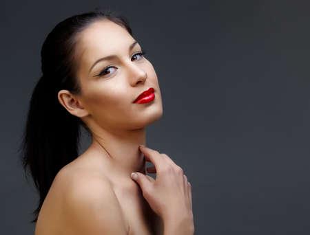 belle femme aux cheveux noir en queue de cheval et de la peau luisante portant le rouge à lèvres rouge classique et la texture de la peau belle Banque d'images