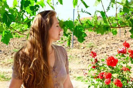 Beautiful woman in 50s with long red hair enjoying sunny summer day the on a wine farm with rose garden. photo