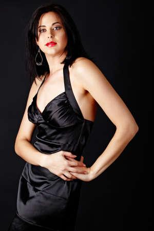 Beautiful brunette fashion model in a black silk dress over a dark studio background wearing red lipstick.  photo