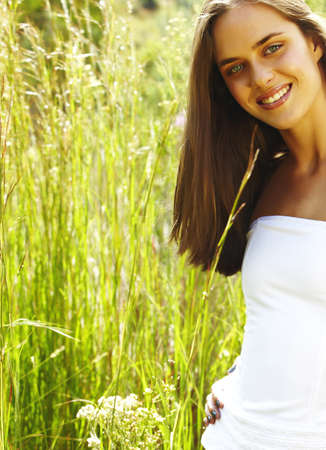 happy beautiful young teenage woman with long brunette hair standing in shorts in tall grass in the field photo