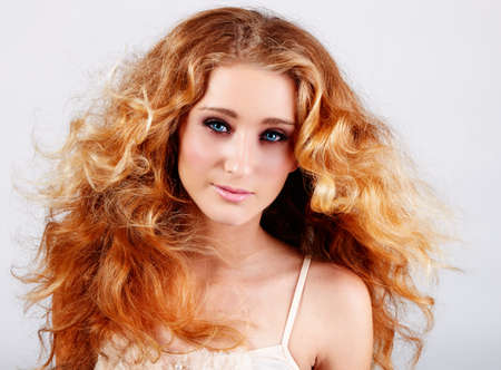 loose hair: bella ragazza con i capelli rossi e gli occhi azzurri che soffia su sfondo grigio in studio Archivio Fotografico