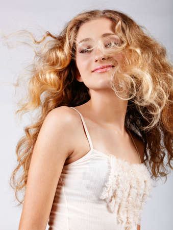loose hair: beautiful strawberry blond teenage girl with  long curly hair blowing in wind over grey studio background Stock Photo