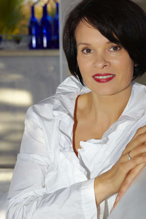Beautiful brunette woman with short hair wearing white blouse in her fifties. photo