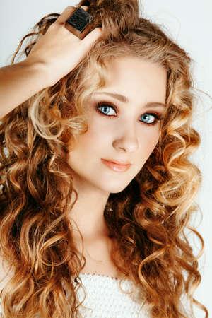 vacker jordgubbe blond kvinna med blå ögon och långa stora lockigt hår med handen i håret