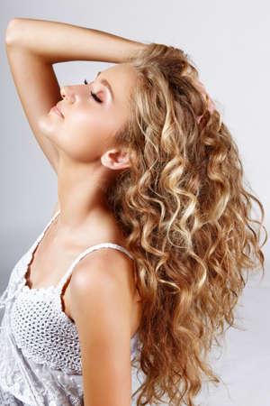 Belle fraises blonde adolescente aux cheveux frisé longs sur fond gris studio.