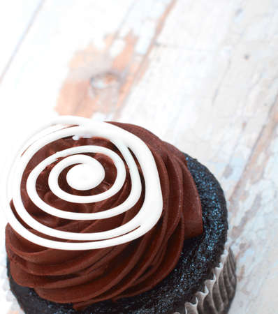 Chocolate cupcake with chocolate mousse cream icing on grunge wooden background with copy space photo