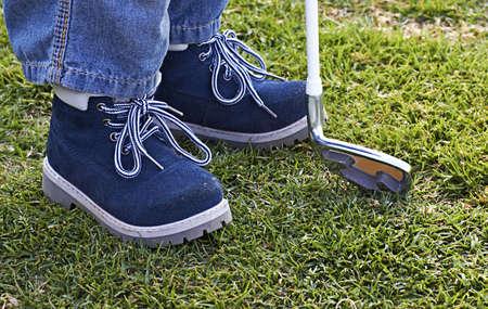 chaussures en cuir d'un petit garçon sur le terrain de golf avec club de golf.