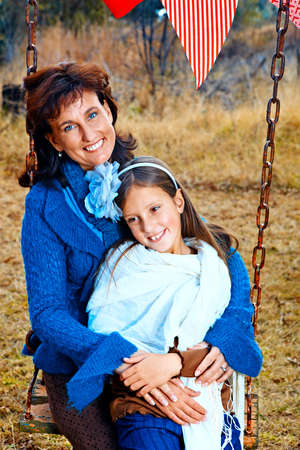 mother and daughter having fun in the outdoors garden on the swing during autumn party photo