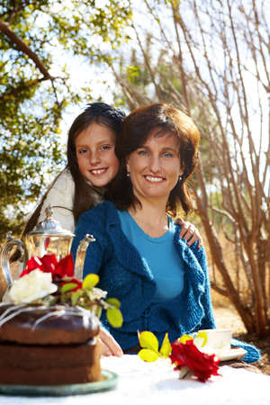 mother and daughter having tea garden birthday party with chocolate cake and roses. photo