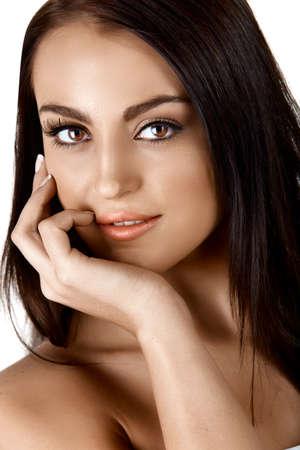 belle femme italienne tannée toucher son visage appliquant la crème et souriant sur fond blanc Banque d'images