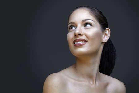 beautiful woman with natural make-up and long lashes on dark studio background photo