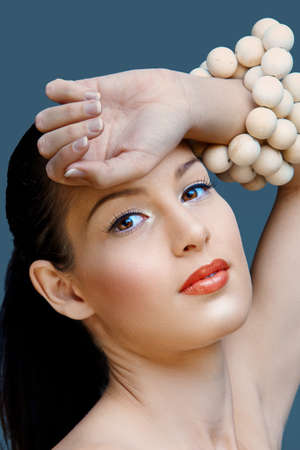 beautiful woman with brown eyes and coral lipstick holding hand against her face on blue studio background. photo