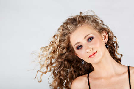 beautiful strawberry blond happy teenage girl with green eyes and long curly hair blowing in wind over grey studio background . Stock Photo - 10645816