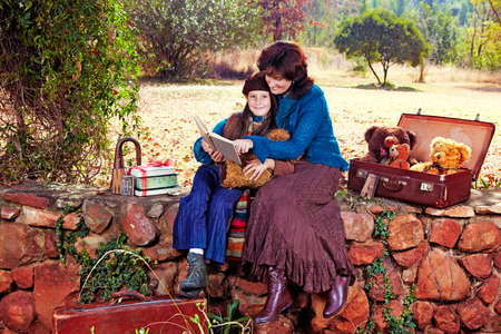 mother and daughter reading vintage books sitting on the wall in the garden with bears on a sunny atumn day. photo