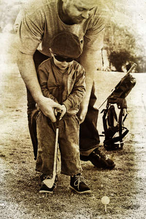 father teaches his toddler son how to play golf in sepia vintage texture