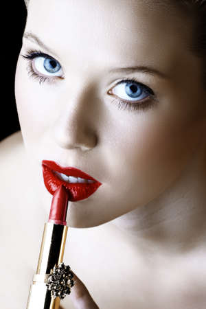 Beautiful young woman with bue eyes applying red lipstick Stock Photo - 10645800