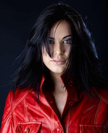 loose hair: bella donna in giacca di pelle rossa e capelli che soffia sul fondo studio scuro