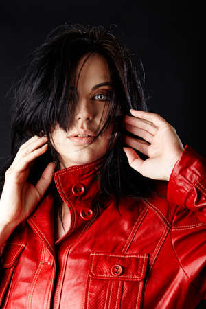 red head: beautiful woman in red leather jacket and blowing hair on dark studio background.