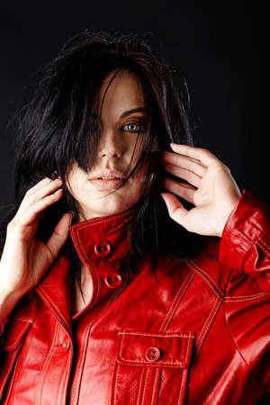 loose hair: bella donna in giacca di pelle rossa e capelli soffiando su sfondo scuro studio.