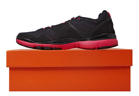 fun black and pink leather fitness sport shoe on the orange box isolated over white. photo