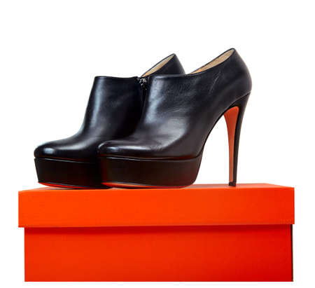 leather black shoes with high heel standing on a red box over white background. photo