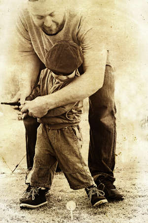 teaches: father teaches his toddler son how to play golf in sepia vintage texture. Stock Photo