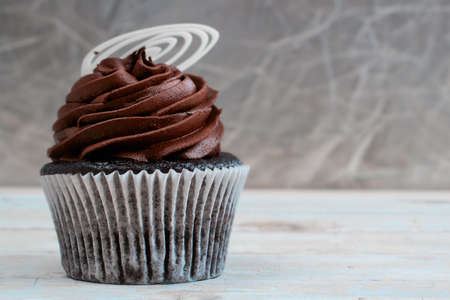 frosted: Chocolate cupcake with chocolate mousse cream icing on grunge wooden background with copy space