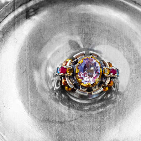 artistic hand made ring with ruby, sapphire, tourmaline gemstones set in Ottoman style hammered silver and bronze over vintage texture photo