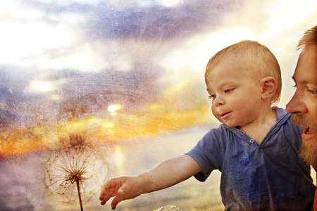 Small baby boy held up by his father reaching for a seed dandelion with grunge texture applied for a rustic effect. photo