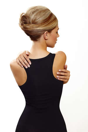 beautiful woman wearing hair in french roll updo in sexy black dress standing with her back against white background Stock Photo