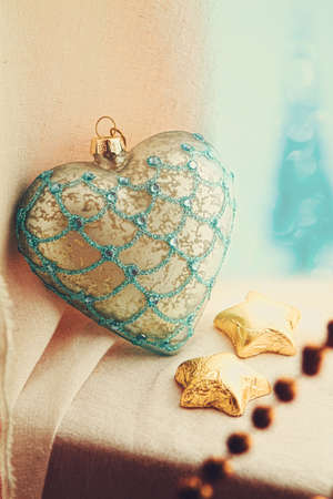 Christmas vintage heart glass decoration with gold stars in the window. photo