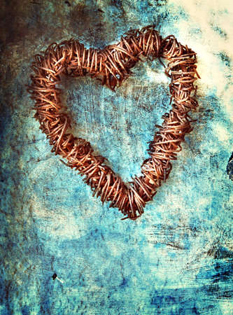 rusted wire heart wreath on painted blue grunge wall background with space for text. Banque d'images