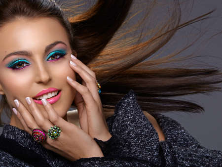 beautiful Italian young oman with fashion bright make-up smiling with hair blowing in the wind. photo