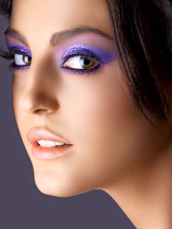 face of Italian beautiful woman with purple eyeshadows and soft smile.. photo