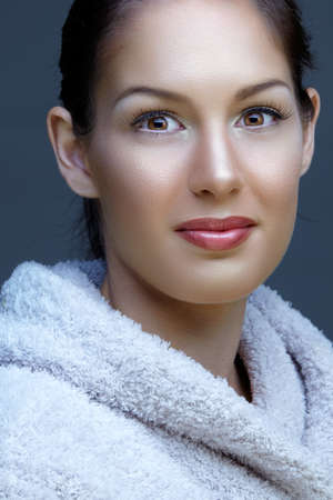 beautiful young smiling woman with natural make-up in a bath robe on studio background. photo