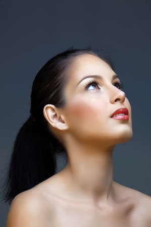 vacker kvinna med långt brunt hår i hästsvans på studio bakgrund bär naturlig make-up Stockfoto