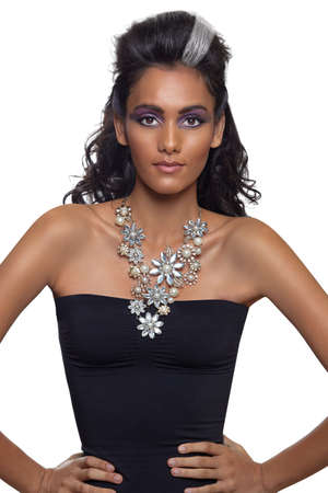 portrait of a beautiful young woman with long curly hair and tanned skin wearing an expensive necklace and black dress.  photo