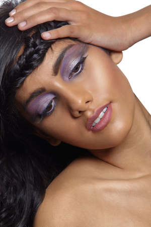 beautiful woman with dark tanned skin and long curly black hair with braid wearing purple artistic make-up with long eyelashes. photo