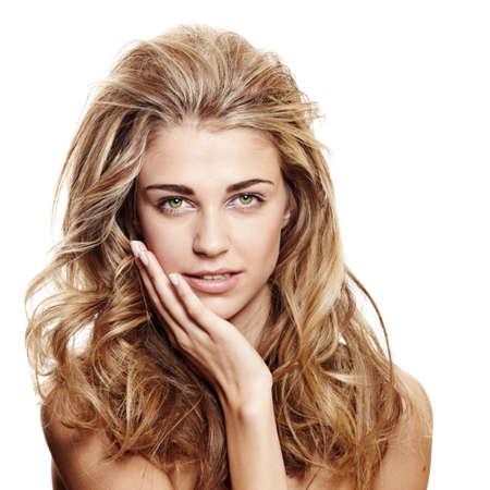 belle femme souriante avec de longs cheveux blonds bouclés et maquillage naturel sur fond blanc toucher son visage
