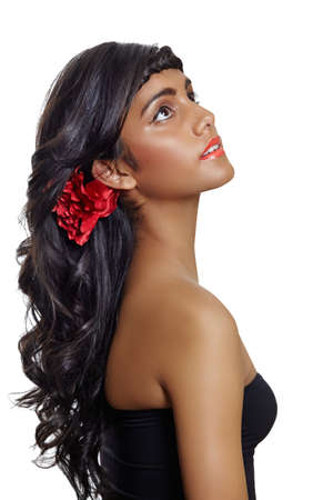 portrait of a beautiful tanned young woman with long brown curly hair and red flower, wearing red lipstick and black dress, sitting in profile on white background Stock Photo